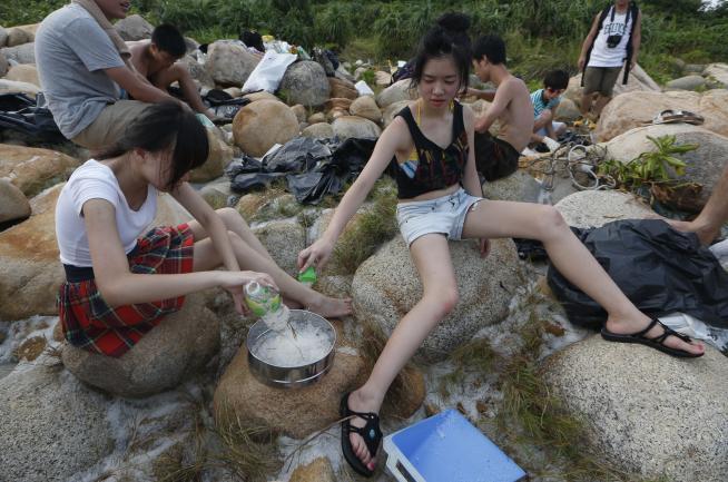 Centinaia di volontari e ambientalisti si sono radunati sulla spiaggia di Lamma Island ad Hong Kong